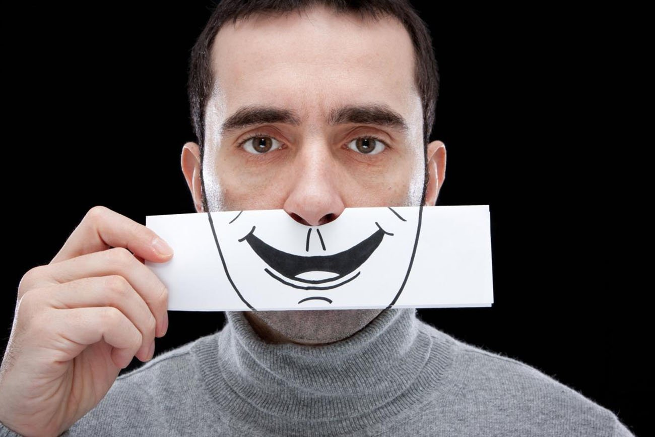 A man hiding his face with a simling sticker probably because he doesn't want to give into emotions as a way to deal with toxic people